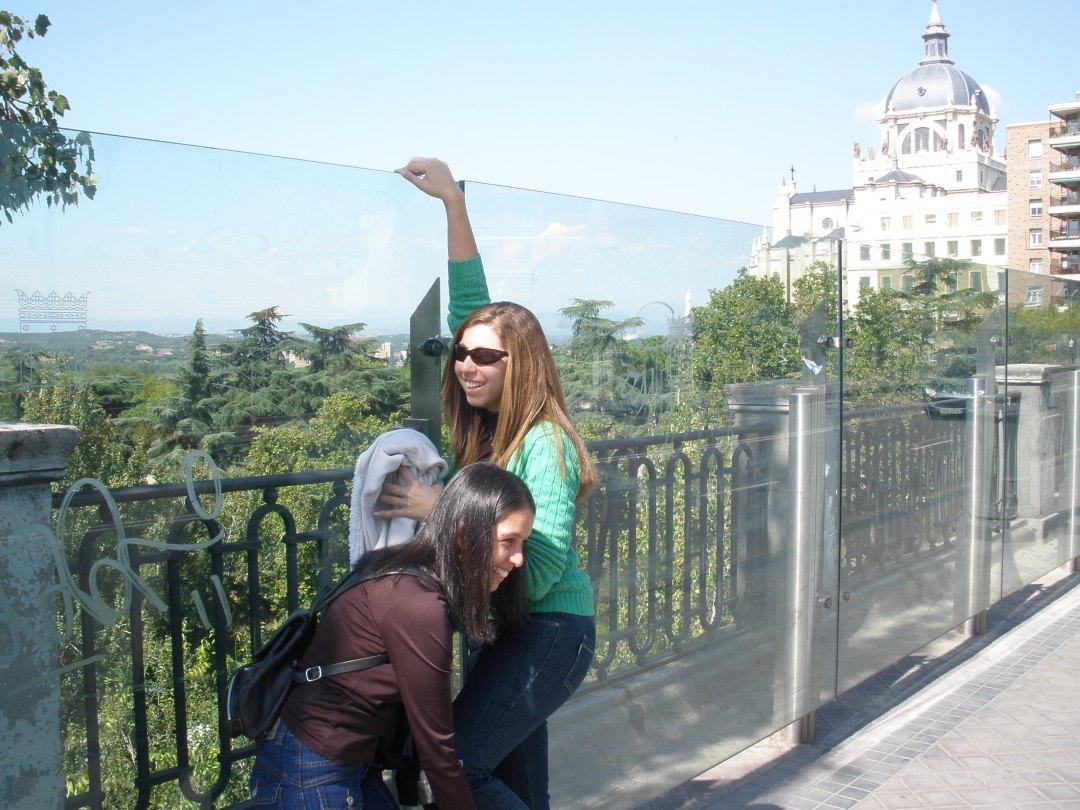 Estamos eu e minha amiga na ponte, ela está fazendo pézinho para eu pular pelo vidro. Estamos meio de lado e estou com a mão direita apoiando no topo do vidro.