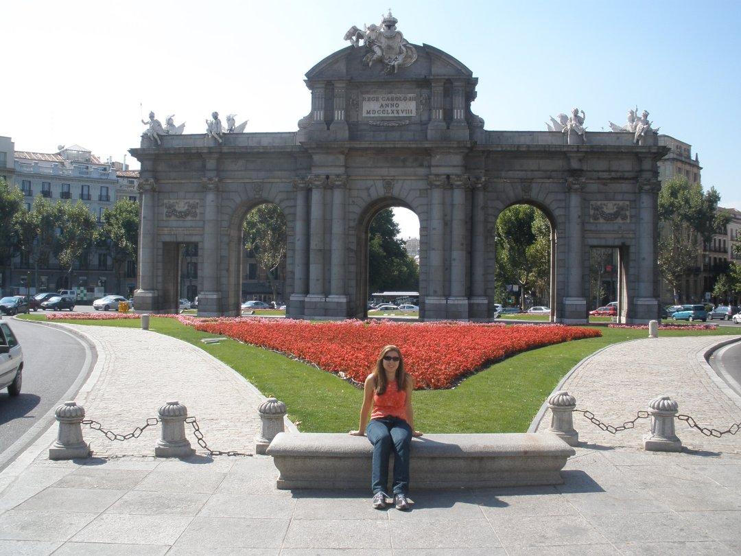 Estou sentada em uma praça e ao fundo a Porta de Alcalá, possui duas portas retangulares que estão ao lado de três arcos