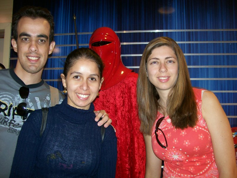 Da esquerda para direita: Meu irmão da minha amiga, minha amiga e eu. Foto da cintura para cima dentro da loja do Star Wars, aarece a cabeça de algum boneco atrás de nós.